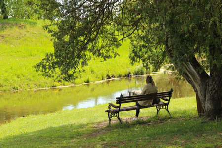 A woman sits on a wooden bench near the water. A lonely woman is in a public park. 免版税图像
