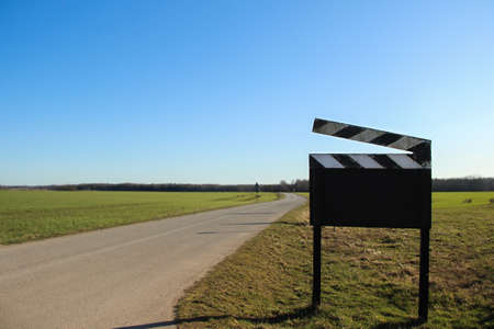 Cinematographic clipboard that stands on the road. Blank clapper board sign that stands outside.