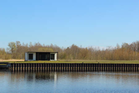 One-storey modular house that stands at the river shore. Container housing that stands aside from the living area. Archivio Fotografico