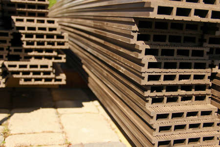 Profile view of composite decking planks put in a pile. WPC decking. Banco de Imagens - 151120411