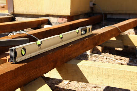 Level check of a wooden beam. Building level in use. 版權商用圖片
