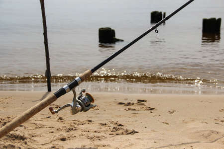 Fishing pole with reel and fishing line stands at the shore.