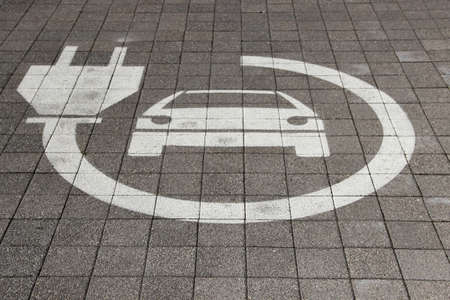 Electric car sign on road. Pictogram at the parking place. Car charging icon.