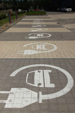 Parking lots for electric cars only. Charging stations stand in a row. Electric car sign. 免版税图像