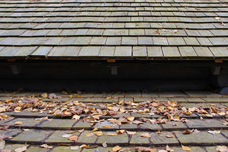 Layered roof made of wooden shingles. Shingle roof covered with dry leaves.