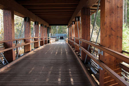 Pedestrian trail covered with roof. Wooden bridge construction. Bridge with railings. 免版税图像