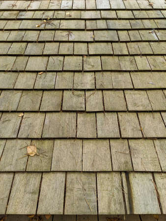 Old wooden shingle texture. Roof covering. Weathered roof tile.