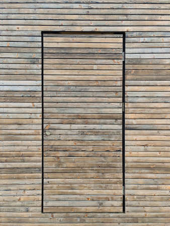Wooden surface with a built-in door. Abstract wooden background. Door made of wooden planks. 免版税图像