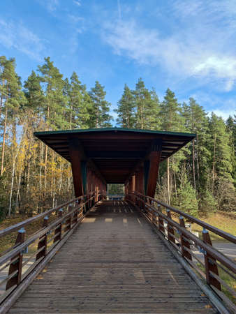 Wooden boardwalk leads to the nature park. Wooden bridge with roof.