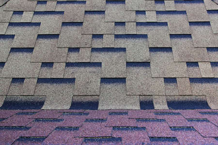 Asphalt roofing in a symmetrical pattern. Composite shingle. Repeating tile.