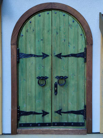 Wooden double barn door with rounded corners. Wooden plank door with forged metal parts.