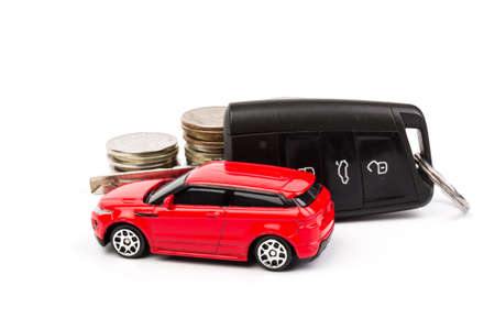Red car and key with coins on white background. Concept of the automobile loan, saving money for car, trade car for cash, the concept of Finance.