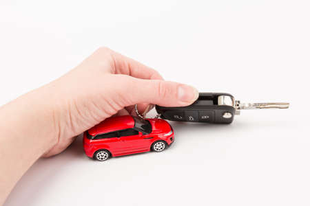 Red car and key in hand. Concept of the automobile loan, saving money for car, trade car for cash, the concept of Finance.