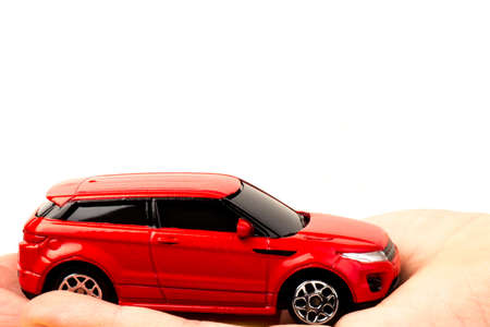 Red car in hand. Concept of the saving money for car, the concept of Finance.