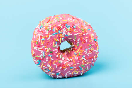Donuts with strawberry icing and multicolored sprinkles, isolated on blue background. Traditional sweet pastries. Place for text. Standard-Bild - 167151019