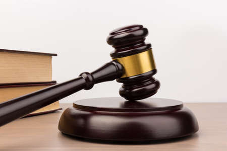 Brown wooden judges gavel on the table in close up. Wooden table, books. Space for text. Law and Justice theme