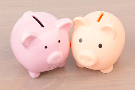 two pink Piggy bank on wooden background, space for text. Finance, saving money. Business to success and saving for retirement concept