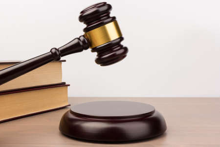 Brown wooden judges gavel on the table in close up. Wooden table, books. Space for text. Law and Justice theme Stock Photo