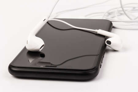 Headphone and phone on white background in close up. Ready to listen to music. Standard-Bild