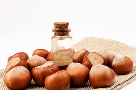 Concept of organic vegetable oils for cooking and cosmetology. Hazelnut nuts to illustrate ingredients. Natural oil in glass bottle. Banque d'images