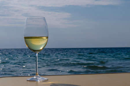 A glass of white wine. Wine against the backdrop of the sea coast and a sunny summer beach. Wine tasting and relaxation at the resort