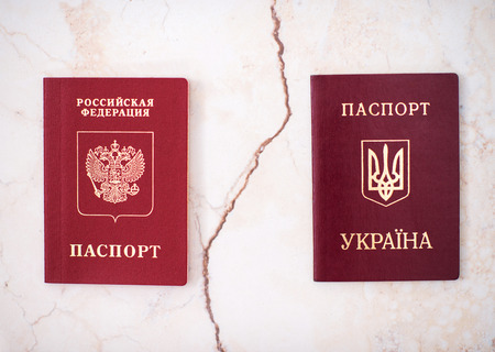 Shchelkovo, Russian Federation - Mar 09, 2019: Two foreign passports  of citizen Russian Federation and Ukraine on white background, the concept of a crack in a relationship between countries