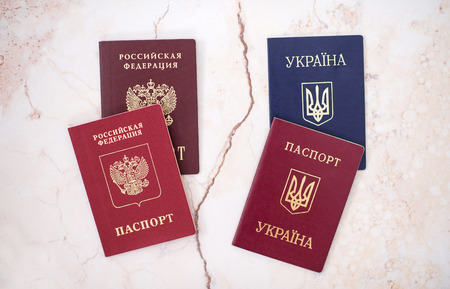 Shchelkovo, Russian Federation- Mar 09, 2019:Four passports foreign and national passports of the Russian Federation,Ukraine on white background, the concept of a crack in relations between countries 写真素材