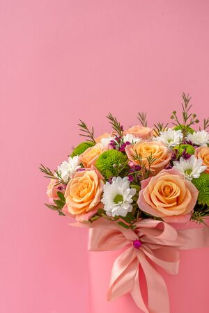 Beautiful bouquet in a pink luxury present box, isolated on pink background