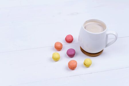 White Cup of fragrant cappuccino with macaroni cakes on white background, top view