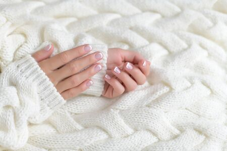 Woman's hand with French manicure isolated on white background