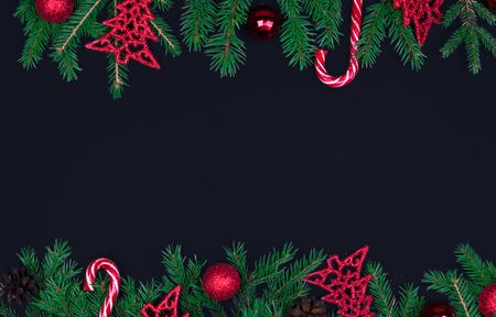 Spruce branches, Christmas balls, candy on a black background, preparing for the New year and Christmas, top view Flat lay