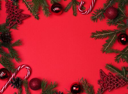 Spruce branches, Christmas balls, candy on a red background, preparing for the New year and Christmas, top view Flat lay