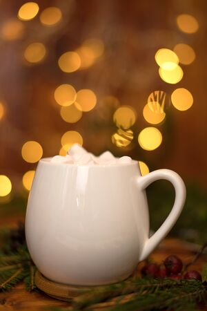 sweet cocoa in a white cup with marshmallow on the background of bokeh lights, Christmas drink. Christmas decoration and bokeh of light in background Zdjęcie Seryjne