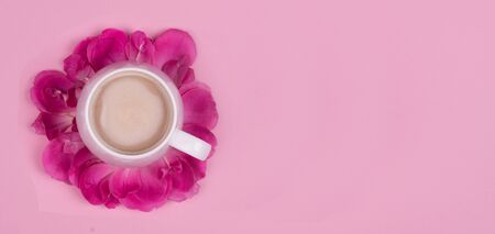 Cup of coffee in rose petals on a pink background, top view
