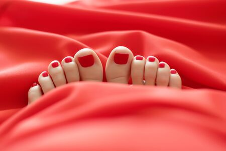female feet with red pedicure under the red covers Close-up of covered female feet with red pedicure, warm, cozy