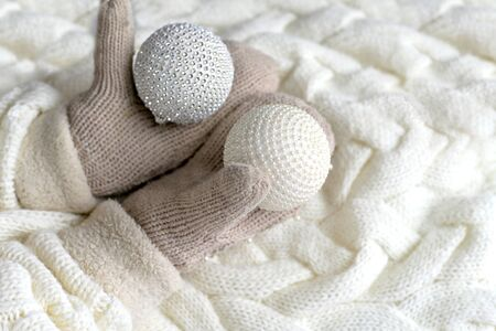 Christmas balls in the hands of mittens on a white knitted background. the concept of winter Banco de Imagens