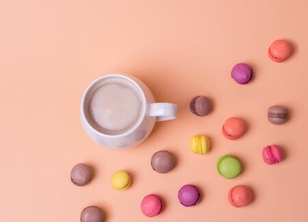 White Cup of fragrant cappuccino with macarons cakes on orange background, top view