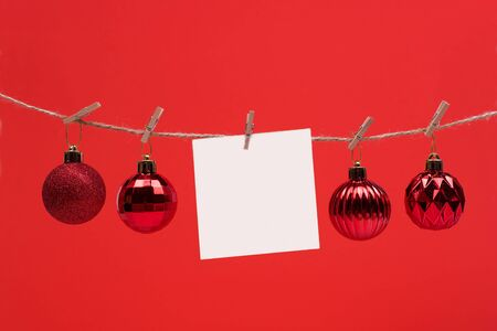 sheet of paper for notes hanging clothespins on red background whith Christmas ball , copy space. wishes 2020 Imagens