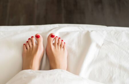 female feet with red pedicure in bed from under the white covers Close-up of covered female feet with red pedicure, warm, cozy Stockfoto