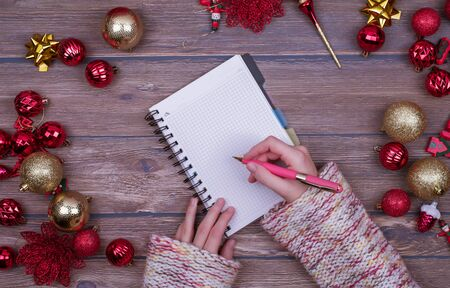 Woman hands write Christmas checklist, letter to Santa on wooden background with christmas ball. Flat lay.