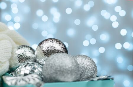 Blue box with silver Christmas balls on the background of blue bokeh lights