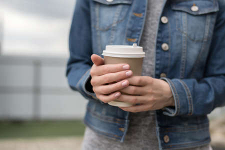 Womens hands in a denim jacket hold a Cup of coffee to go, zero west Imagens