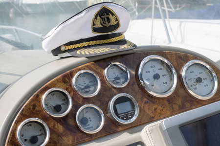 White sea captains cap on the dashboard of the boat