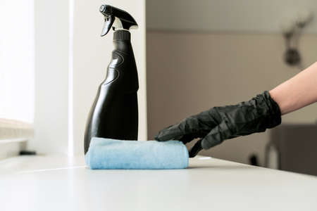 A hand in black gloves holds a microfiber cleaning cloth and a spray with sterilizing make disinfection for good hygiene