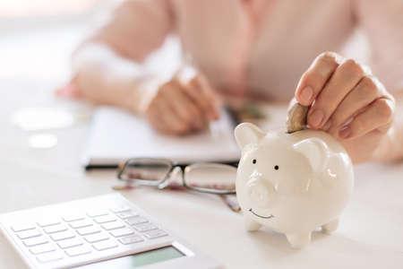 Old women's hands put money in the piggy Bank, the concept of retirement, savings. Standard-Bild