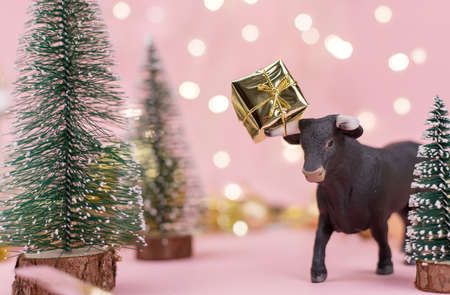 Decorative bull symbol of New Year on the pink background of Christmas tree and bokeh