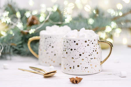 White cup of cappuccino or cocoa with christmas tree on the buckground of gold bokeh, New Year hot drink. Stockfoto