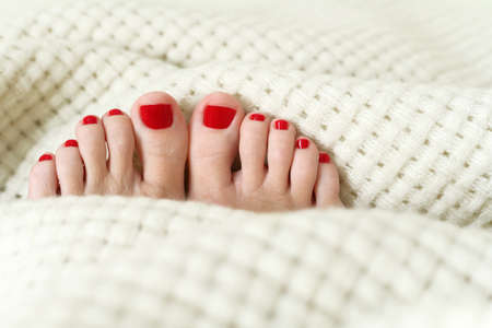 Red winter pedicure on white warm plaid.