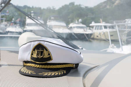 White sea captain's cap on the dashboard of the boat.