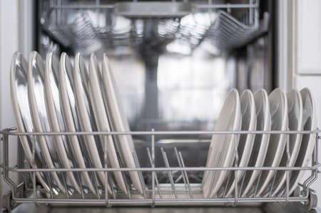 White flat plates large and small are loaded into the dishwasher